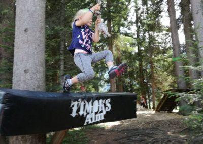 Ein Kind schwingt sich mit dem Seil von Baum zu Baum