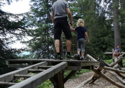 Papa und Tochter gehen über ein Holz-Hindernis