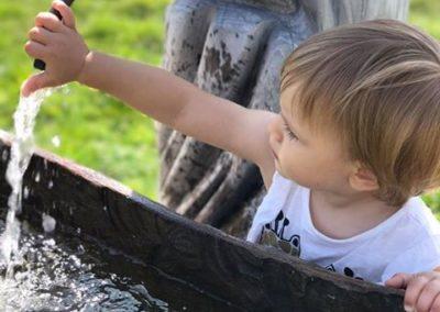 Ein Kind spielt mit Wasser, das aus einem Brunnen kommt