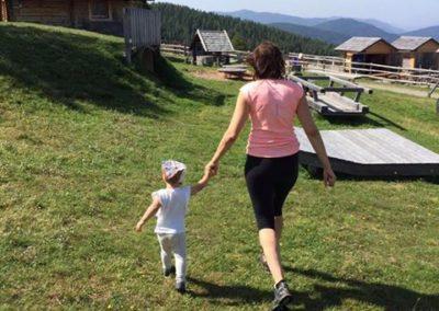 Mama geht mit Kind zum Almspieplatz