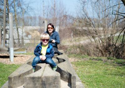 Bub sitzt auf Holz und Mama dahinter
