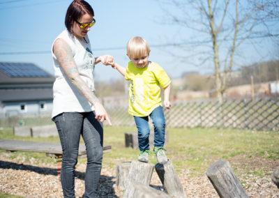 Mama hilft Sohn beim Balancieren auf Baumstämmen